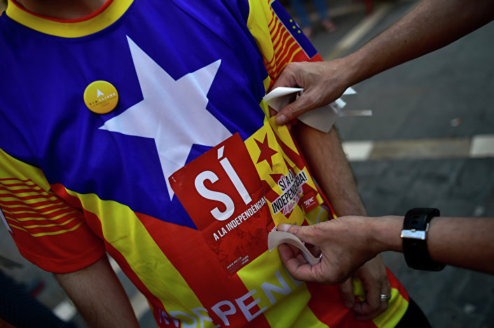 A pro-independence Basque puts a sticker on a T-shirt which reads, ''Yes for the Independence'', during a march to support the pro-independence Catalonia movement, in Pamplona, northern Spain, Saturday, Sept. 11, 2015
