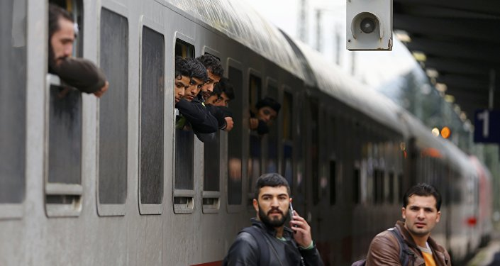 Migrants lean out of windows as their train arrives in Freilassing, Germany September 28, 2015