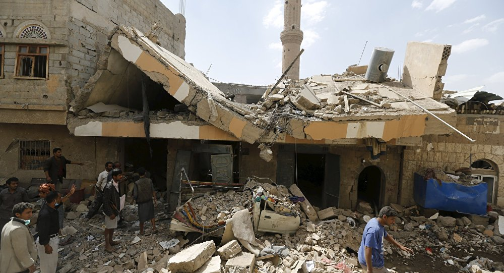 People walk at the site of a Saudi-led air strike in Yemen's capital Sanaa September 21, 2015