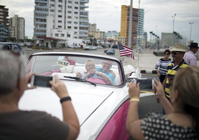 U.S. citizens pose for photos as they enjoy a ride in a vintage car at the seafront Malecon during a cultural exchange trip in Havana, September 28, 2015