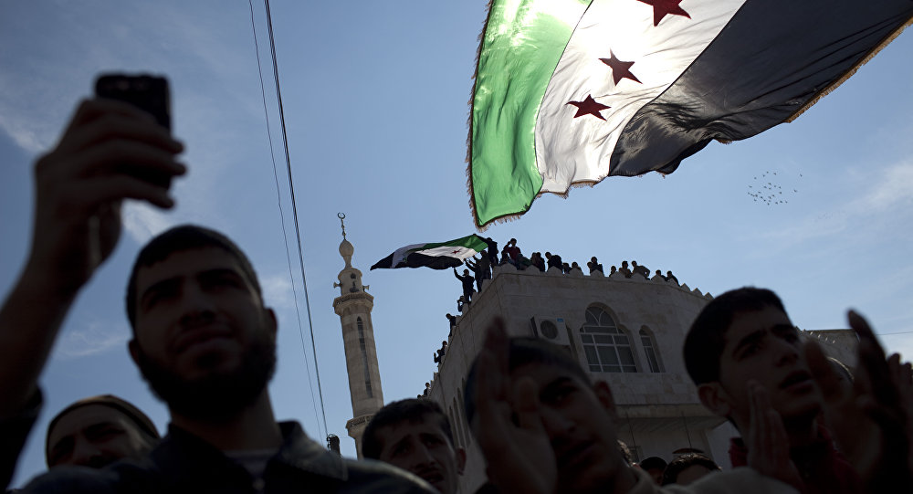 In this Friday, March 2, 2012 file photo, men hold revolutionary Syrian flags during an anti-government protest in a town in northern Syria.