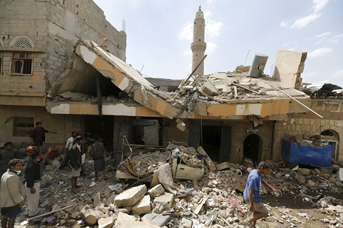People walk at the site of a Saudi-led air strike in Yemen's capital Sanaa September 21, 2015