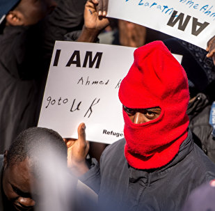 A migrant holds a placard reading 'I am Ahmed. Go to UK' as part of a rally of around 3000 migrants and members of associations aiding migrants including British associations, in the northern French port city of Calais, on September 19, 2015