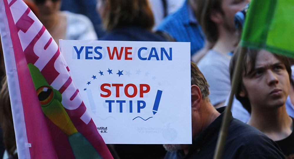 Demonstrators hold a sign against the TTIP contract during a protest.