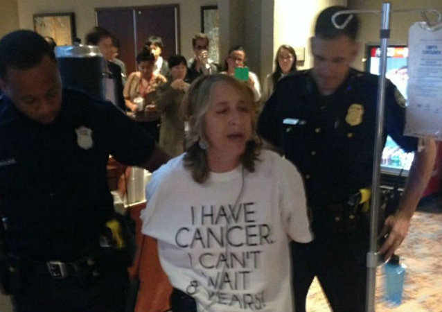 Atlanta police arrest health advocate and cancer survivor Zahara Heckscher outside of negotiations for the Trans-Pacific Partnership.