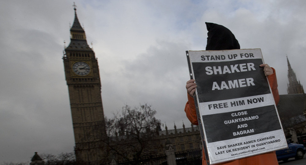 A hooded protester demonstrates for a Guantanamo detainee Shaker Aamer outside the Palace of Westminster in London, Wednesday, Jan. 15, 2014.