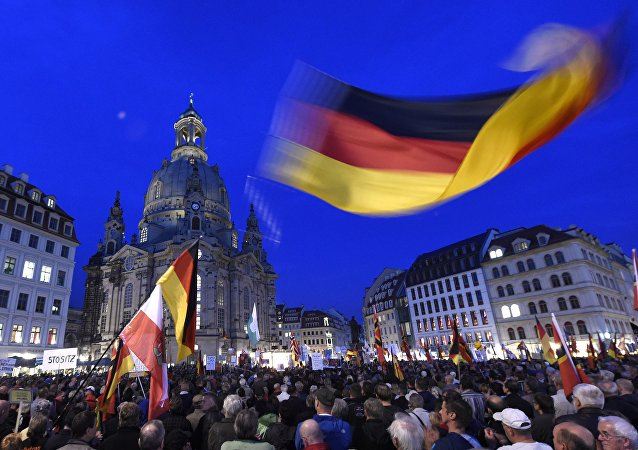 Protestors wave a German flag in front of the Church of Our Lady during a demonstration of PEGIDA (Patriotic Europeans against the Islamization of the West) in Dresden, eastern Germany, Monday, Oct. 5, 2015.