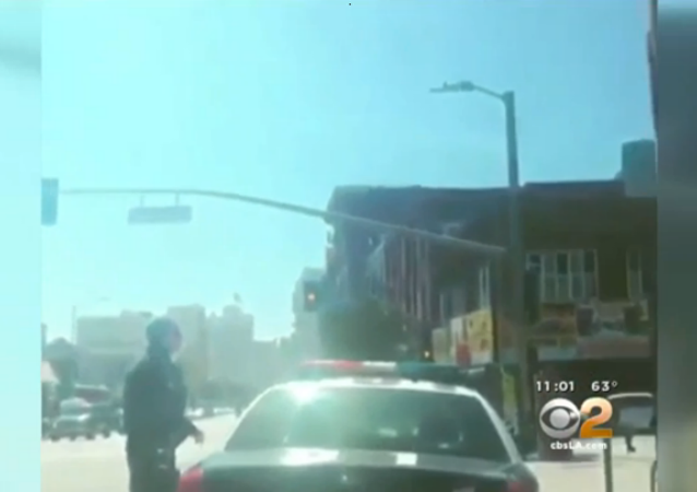 The video footage, posted on social media, begins with a Los Angeles police officer getting out of his patrol car, followed by a shot of a handgun held by a person watching the officer.