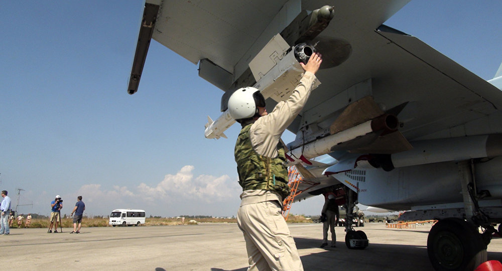 In this photo taken on Monday, Oct. 5, 2015, a Russian pilot fixes an air-to-air missile at his Su-30 jet fighter before a take off at Hmeimim airbase in Syria