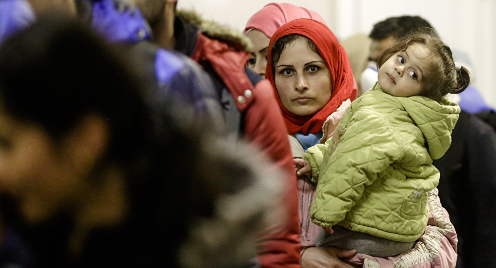 This file photo shows a migrant woman with a child stands in a queue of refugees and migrants after she arrived with a train at the train station Schoenefeld near, Berlin, Germany, Wednesday, Oct. 7, 2015.