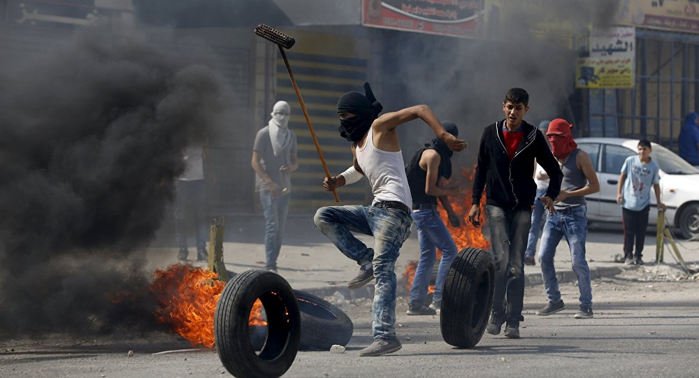 A Palestinian protester moves a burning tyre during clashes with the Israeli army at Qalandia checkpoint near occupied West Bank city of Ramallah October 6, 2015