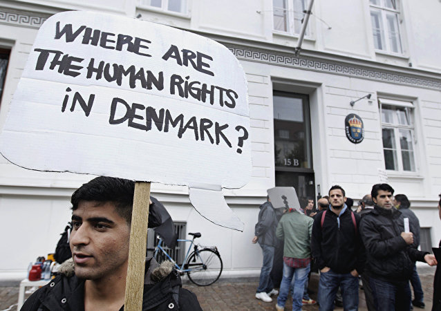 Some thirty Syrian refugees from different camps seeking asylum hold banners outside the Swedish Embassy in Copenhagen, Denmark on Wednesday, Sept. 26, 2012.