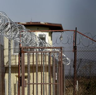 A security guard walks along a fence topped with barbed and razor wire in a facility for a detention of foreigners in the village of Drahonice, western Czech Republic, October 2, 2015.