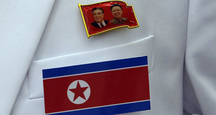 A pin of late North Korea leaders Kim Il Sung and Kim Jong Il and North Korea's flag are displayed on a North Korean reporter's jacket at the Main Media Center for the 17th Asian Games in Incheon, west of Seoul, South Korea