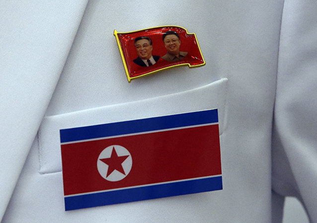 In this Friday, Sept. 12, 2014 photo, a pin of late North Korea leaders Kim Il Sung and Kim Jong Il and North Korea's flag are displayed on a North Korean reporter's jacket at the Main Media Center for the 17th Asian Games in Incheon, west of Seoul, South Korea