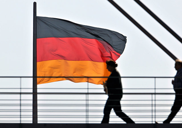 People pass a giant German National flag on the Reichstag, which houses the German parliament Bundestag