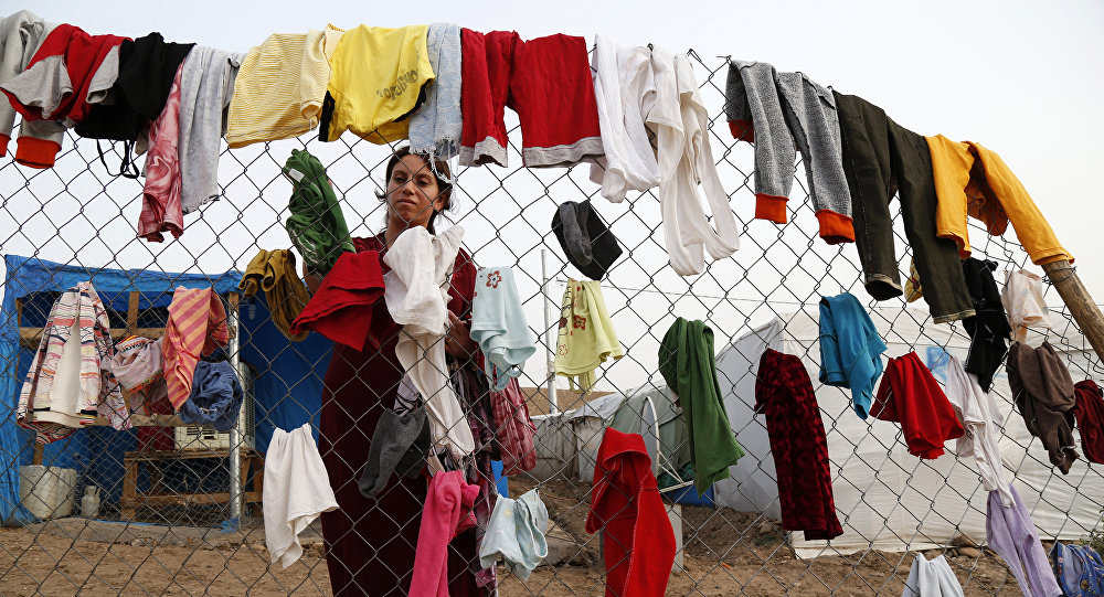 A Syrian refugee woman hangs laundry on a fence at an informal tented settlement in Irbil, northern Iraq.