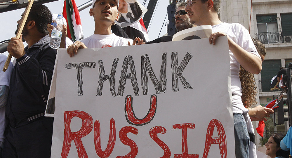 In this Oct. 12, 2011 file photo, supporters of the Syrian government hold a pro-Russian banner to show their support for President Bashar Assad and to thank Russia and China for blocking a U.N. Security Council resolution condemning Syria for its brutal crackdown, during a demonstration in Damascus, Syria.
