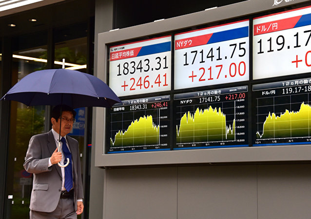 A businessman passes before a share prices board in Tokyo on October 16, 2015