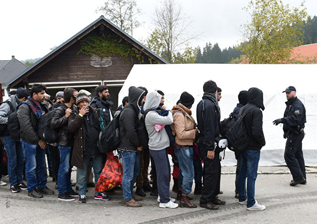 German police officer instructs migrants ahead of their walk from the Austrian-German border to a first registration point of the German federal police in the small Bavarian village Wegscheid, southern Germany, on October 20, 2015