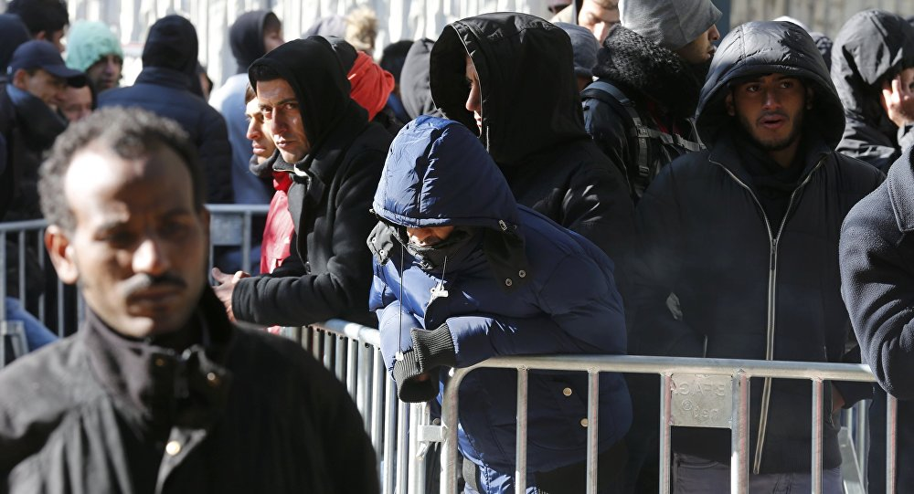Migrants queue in the compound outside the Berlin Office of Health and Social Affairs (LAGESO) as they wait to register in Berlin, Germany, October 12, 2015