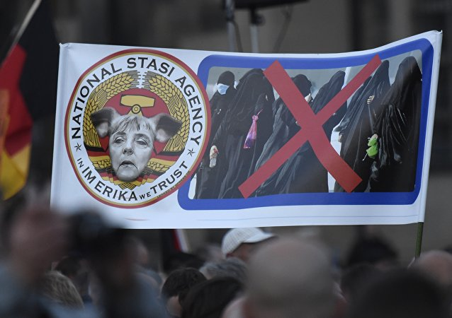 Protesters hold a poster depicting German Chancellor Angela Merkel with pig-ears beside women in burqas during a demonstration of PEGIDA (Patriotic Europeans against the Islamization of the West) in Dresden, eastern Germany, Monday, Oct. 5, 2015.