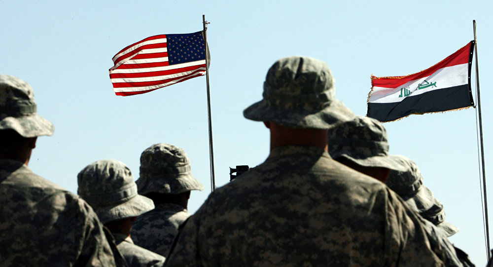 US troops stand to attention in front of American and Iraqi (R) flags during a handover ceremony near the northern Iraqi town of Hawija