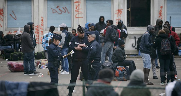 French police stand near migrants who gather in the courtyard of the Lycee Jean Quarre, an empty secondary school occuiped by hundred of migrants and asylum seekers in the 19th district in Paris, France, October 23, 2015