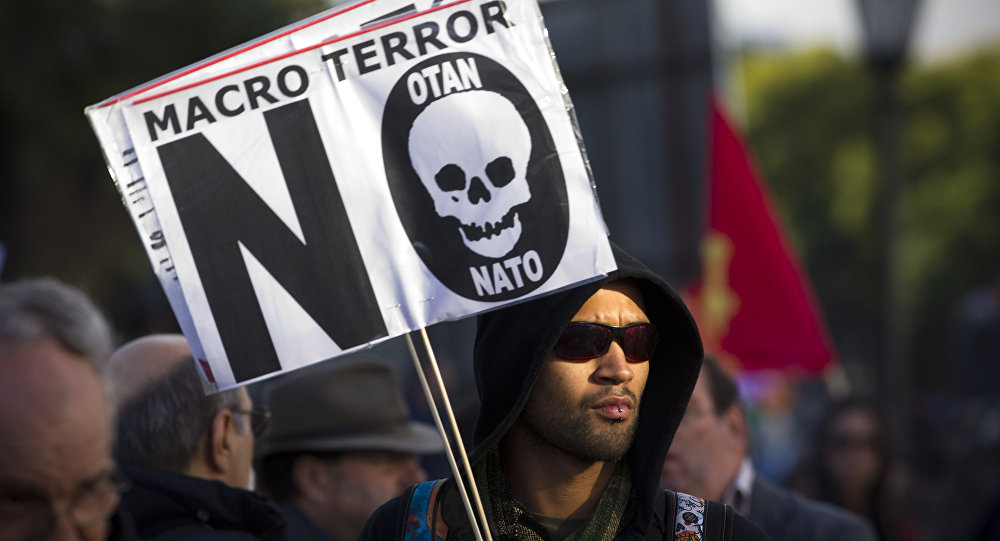 A protester holds a sign that reads Macro terror, no to NATO during a demonstration against NATO in Lisbon, on Saturday, Nov. 20, 2010