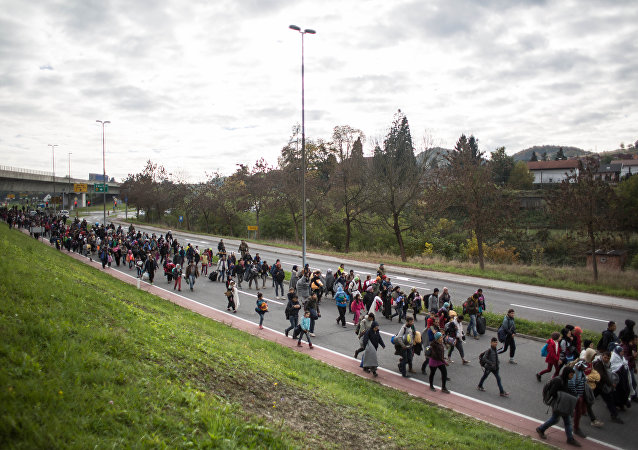 Refugees and migrants walk on a road as they leave Sentilj, Slovenia.