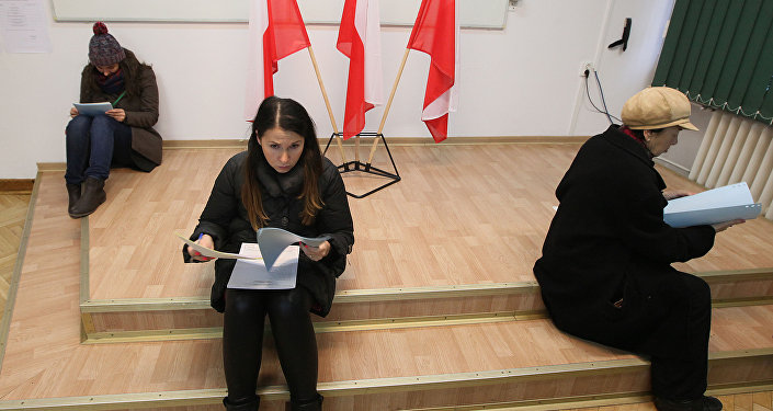 Voters read documents during the first round of Polish local elections in Warsaw, Poland, Sunday, Nov. 16, 2014
