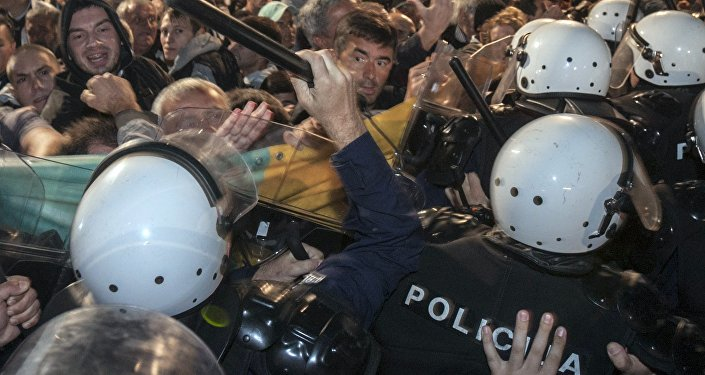 A riot policeman hits Montenegro's opposition leader Nebojsa Medojevic (facing camera, on R of baton) with a baton while dispersing protesters outside the parliament building in the capital Podgorica, Montenegro, October 17, 2015
