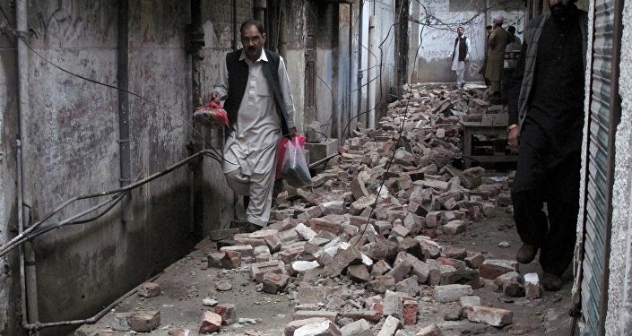 A man with his belongings walks past the rubble of a house after it was damaged by an earthquake in Mingora, Swat, Pakistan
