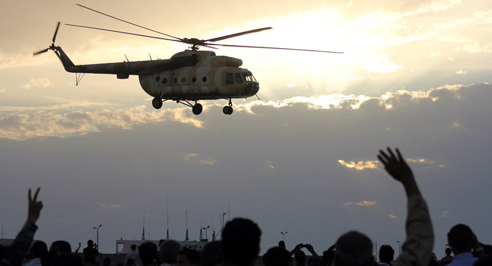 Libyans wave and flash the sign for victory at a military helicopter as flies during a military display in Libya's coastal city of Benghazi on May 15, 2012.