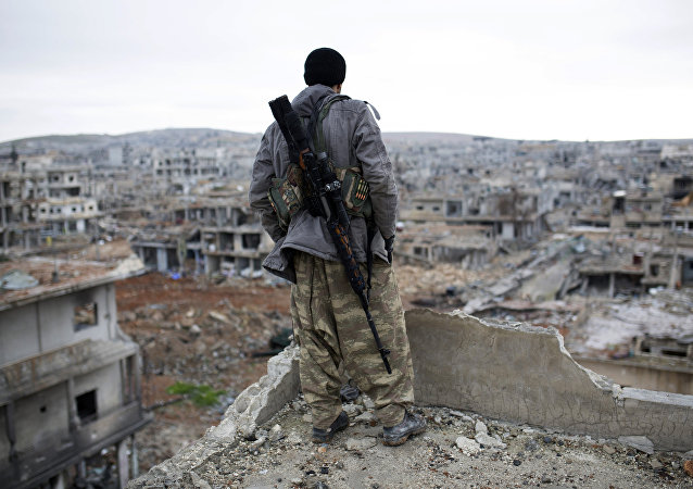 FILE - In this Jan. 30, 2015, file photo, a Syrian Kurdish sniper looks at the rubble in the Syrian city of Ain al-Arab, also known as Kobani