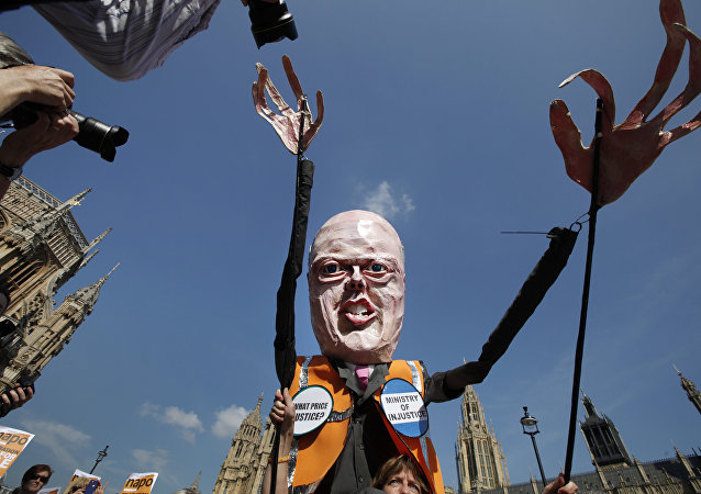 A protester carrying a puppet depicting Chris Grayling in central London, Tuesday, April 1, 2014.