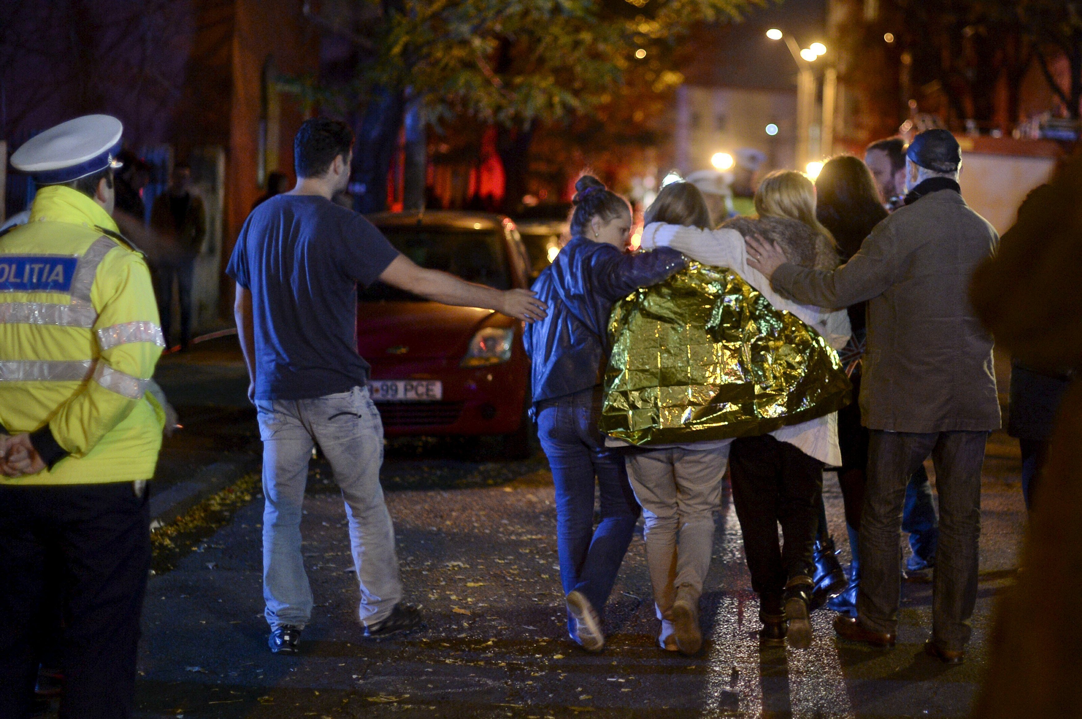 People walk outside a nightclub following an explosion in Bucharest, Romania October 31, 2015. Twenty five died in a nightclub blast and fire late on Friday and at least 88 people were admitted to hospital, government officials said.