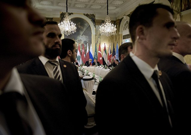 Security staff stand as US Secretary of State John Kerry (back L) and Russian Foreign Minister Sergei Lavrov (back 2nd L) chat before a meeting with 17 nations, the European Union and United Nations at the Hotel Imperial in Vienna, October 30, 2015