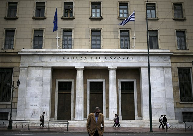 People make their way next to the headquarters of Bank of Greece in central Athens, Greece, October 30, 2015
