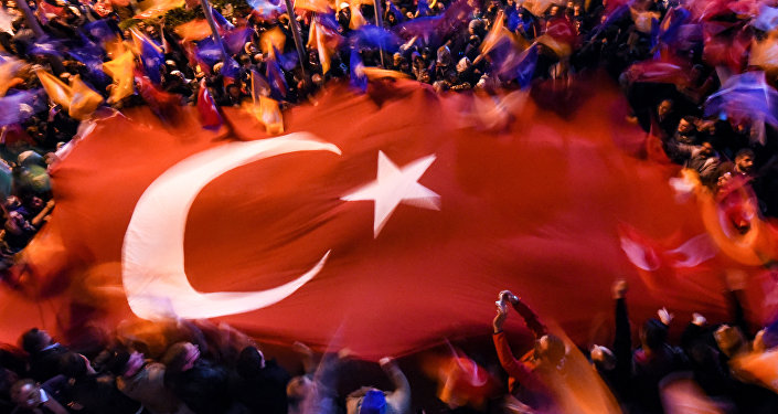 Supporters of Turkey's Justice and Development Party (AKP) wave a giant Turkish flag as they celebrate in Istanbul after the first results in the country's general election on November 1, 2015.