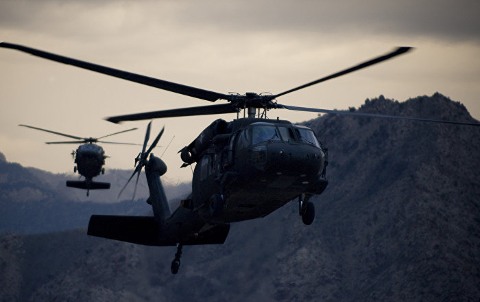 Two Army UH-60 Black Hawk helicopters prepare for landing at forward operating base Kalagush.