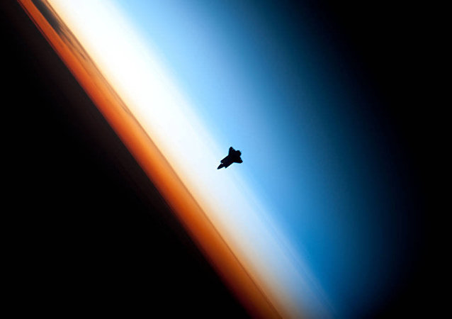 In a very unique setting over Earth's colorful horizon, the silhouette of the space shuttle Endeavour is featured in this photo by an Expedition 22 crew member on board the International Space Station, as the shuttle approached for its docking on Feb. 9 during the STS-130 mission.