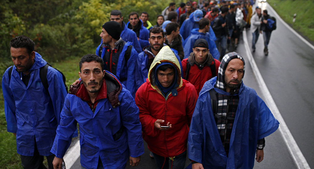 Migrants walk along a road.