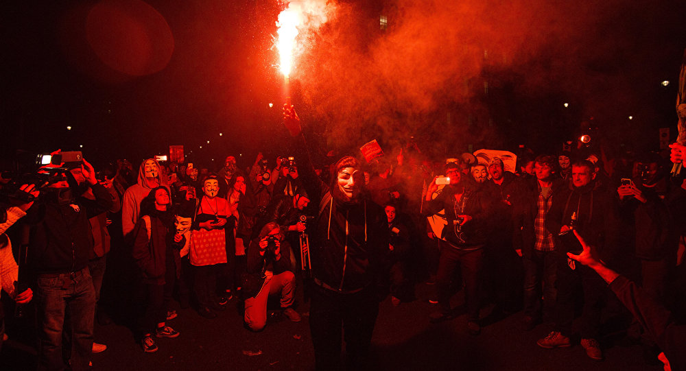 An anti-capitalist protester wearing aGuy Fawkes mask holds a lit flare during the Million Masks March, organised by the group Anonymous, near the Houses of Parliament in central London on November 5, 2015.
