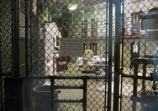 In this photo reviewed by the U.S. military, a prisoner stands with his back turned inside Camp 6, a communal unit of the Guantanamo Bay detention center for prisoners who are considered highly compliant with the rules, at Guantanamo Bay Naval Base, Cuba, Saturday, June 7, 2014