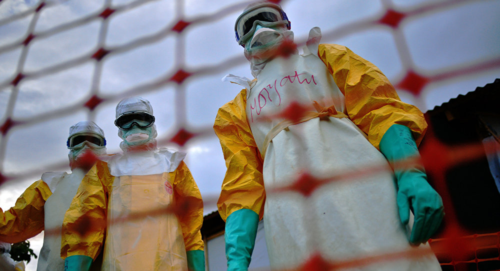 (FILES) A file picture taken on August 14, 2014 shows Medecins Sans Frontieres (MSF) medical staff wearing protective clothing treating the body of an Ebola victim at their facility in Kailahun