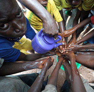 (FILES) A file picture taken on September 3, 2014 shows people washing their hands with soap and bleach to prevent the spread of the Ebola virus