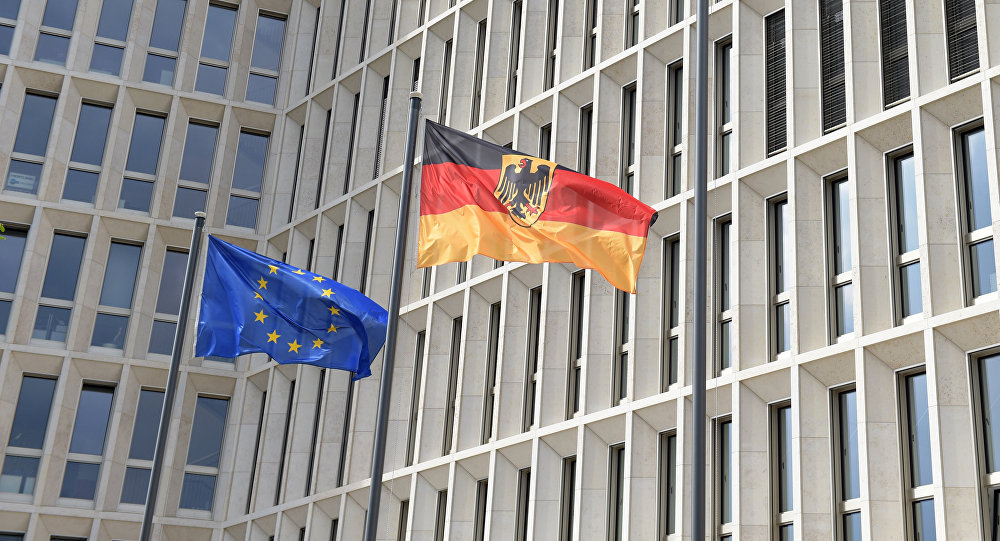 The German (R) and the European flag fly in the wind outside the new Federal Ministry of the Interior building in Berlin on April 26, 2015