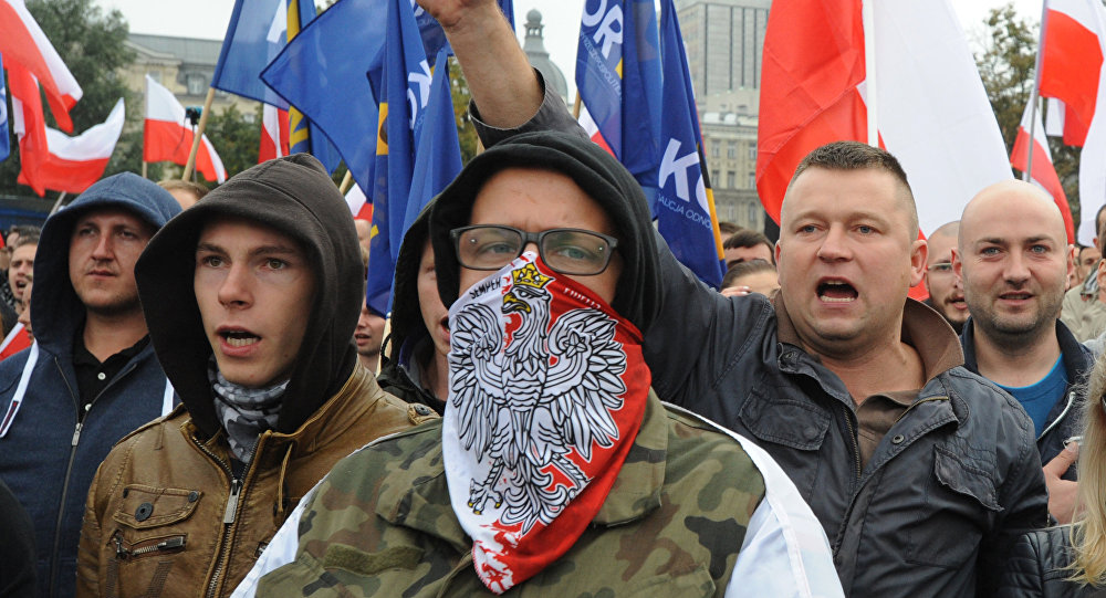 Protesters shout anti migrant slogans as several thousand right wing nationalists march through downtown, demonstrating against EU proposed quotas for Poland to spread the human tide of refugees around Europe, in Warsaw, Poland, Saturday, Sept. 12, 2015