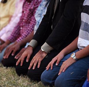 Muslim men kneel to pray